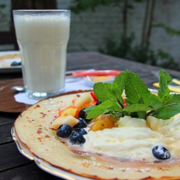 Zum Beispiel Pfannkuchen mit frischen Früchten und weiße heiße Schokolade